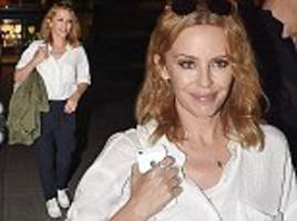 Kylie Minogue ditches her famous hotpants for uncharacteristically casual joggers and a baggy white shirt as she jets into London