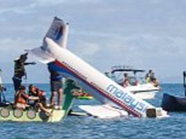 Is this the most tasteless joke ever? Man and his young sons sink a cardboard model of MH370 to win bizarre beach competition... but victim's family does NOT find it funny